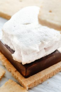 Image of Keto Marshmallows on top of a smore with another graham cracker being placed on top.