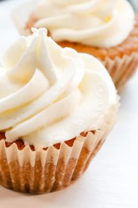 Image of two Vanilla Keto Cupcakes with white frosting side by side.