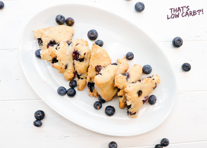 Overhead shot of Low Carb Scones in a line on a oval white plate with blueberries sprinkled around.
