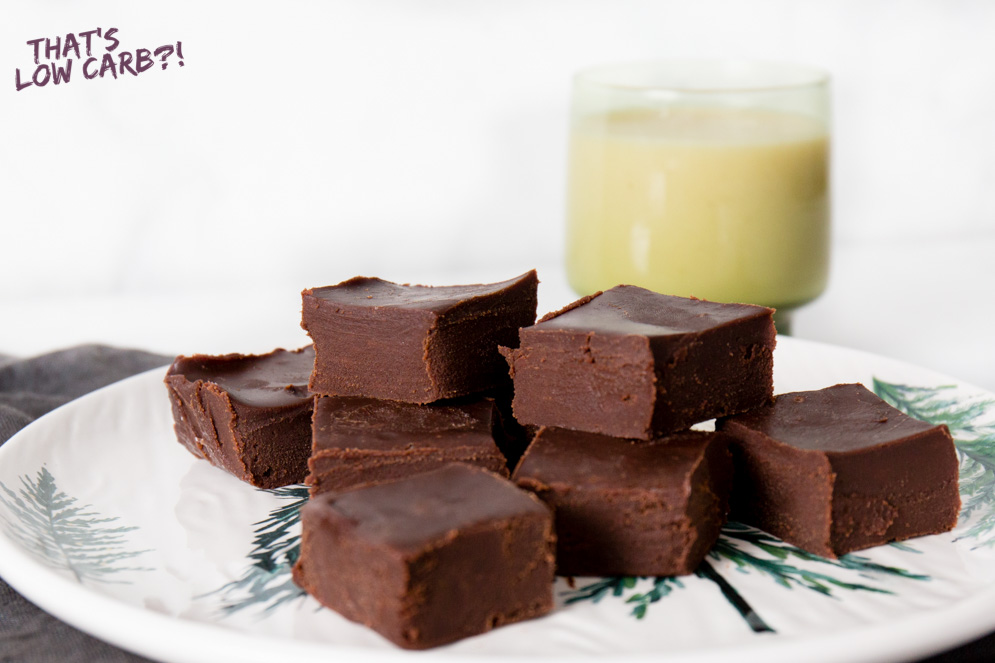 Image of Keto Chocolate Fudge with some stacked on a white plate with a glass of milk blurred in the background.