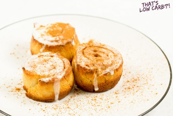 Image of three Keto Cinnamon Rolls on a white plate with cinnamon sprinkled over top.