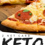 "PINTEREST IMAGE with words ""2 net carb Keto Fathead Pizza Dough"" with image of Keto Fathead Pizza Dough on a wooden cutting board with one slice missing."