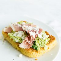 slice of 90 second keto bread on white plate with avocado and prosciutto on top.