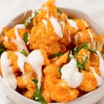 Image of Keto Buffalo Cauliflower Bites in a white bowl with white sauce drizzled over top and green garnish on a white background.