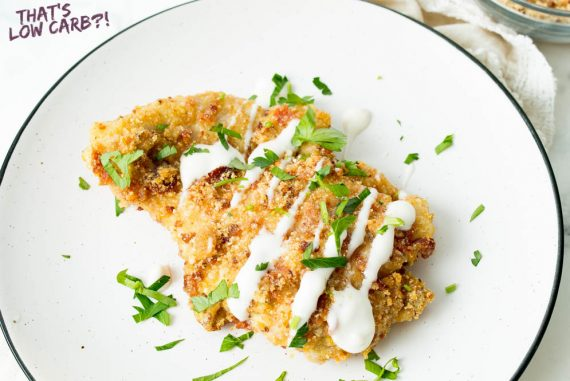 Overhead shot of keto parmesan chicken with white sauce drizzeled over top and green garnish sprinkled around white plate.