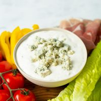 Bowl of Blue Cheese Dressing surrounded by lettuce, tomatoes, peppers and prosciutto