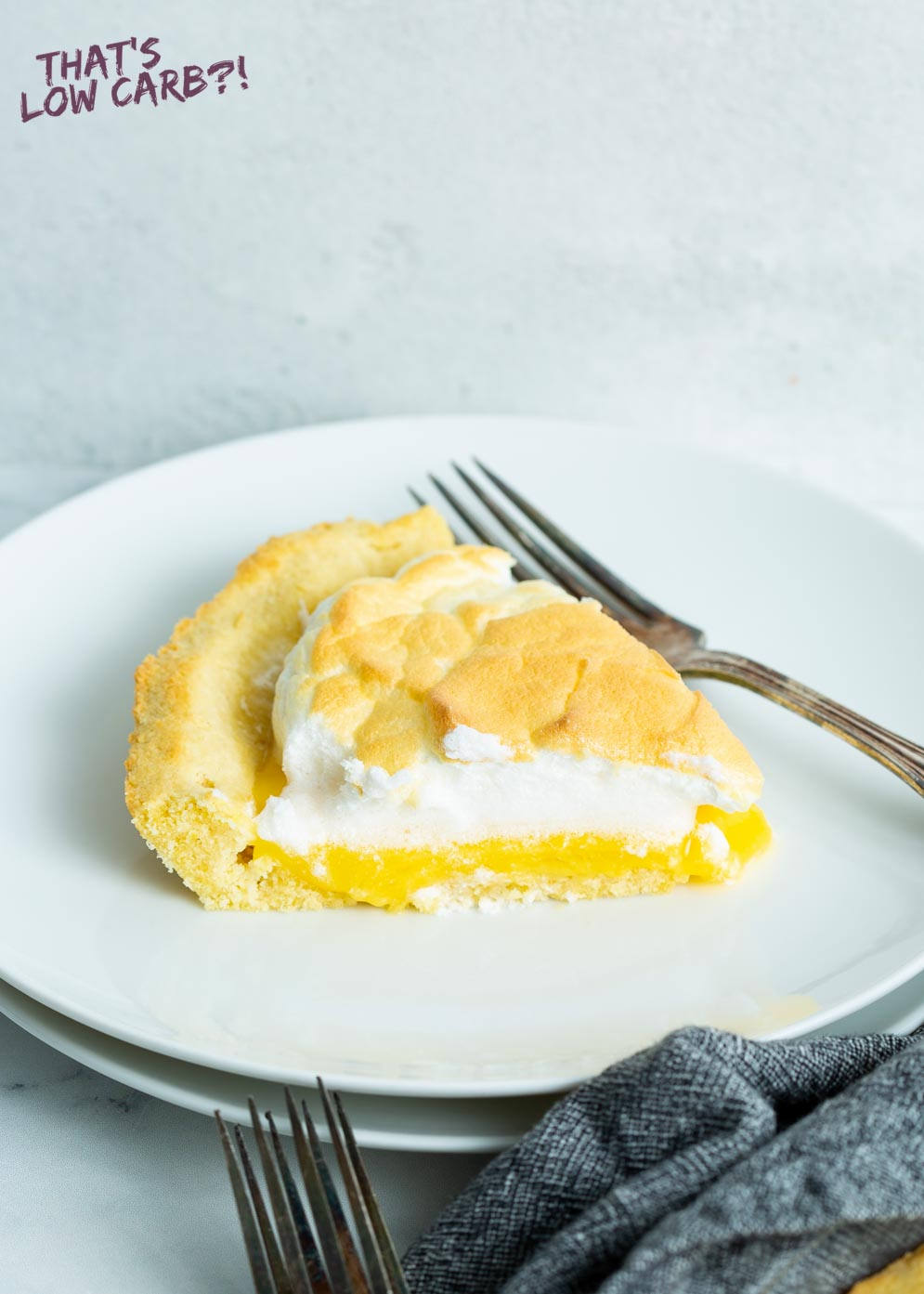 Slice of Sugar-Free Lemon Meringue Pie on small white plate with fork