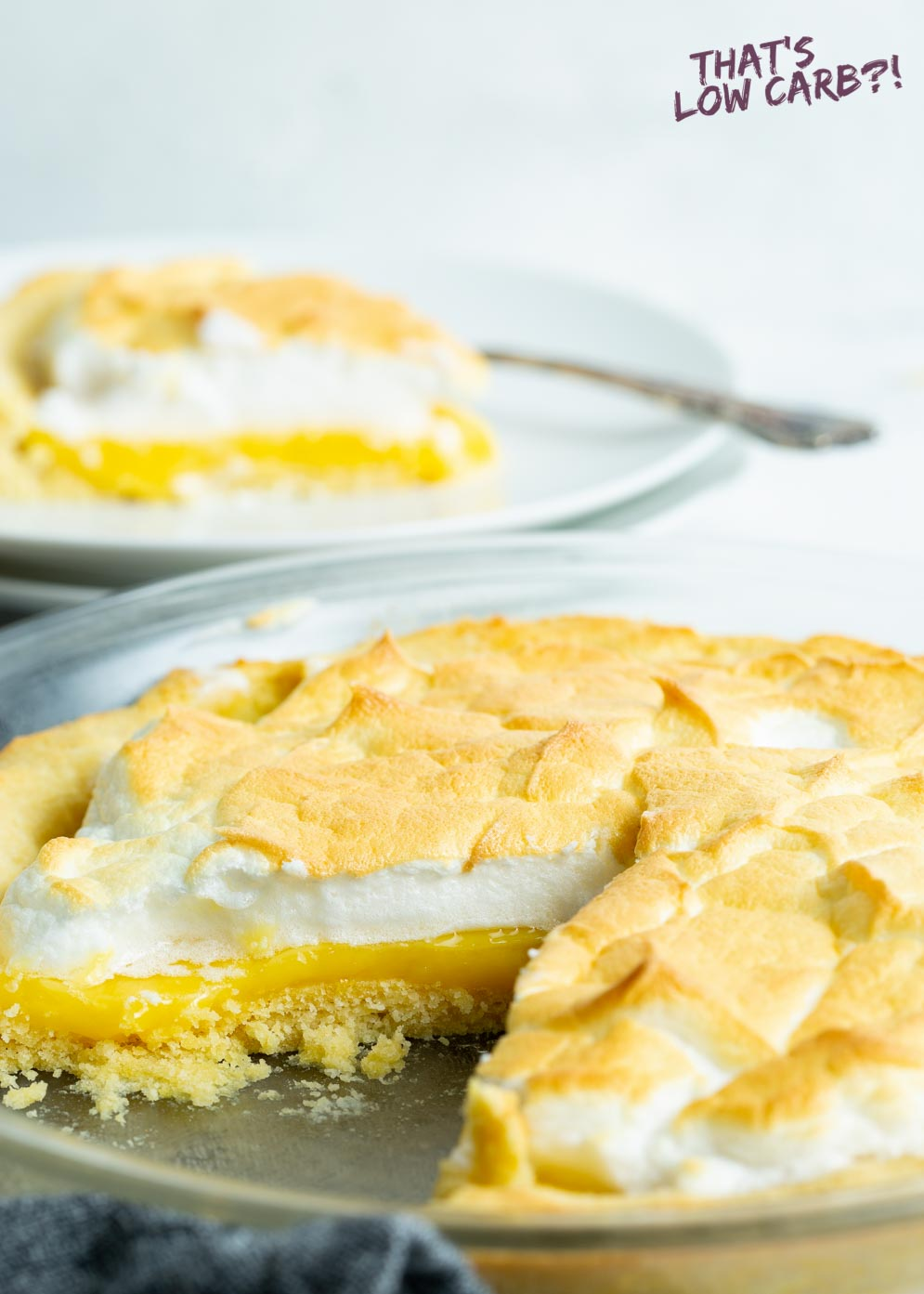 Picture of keto lemon meringue pie with slice take out of and slice of pie blurred out in background