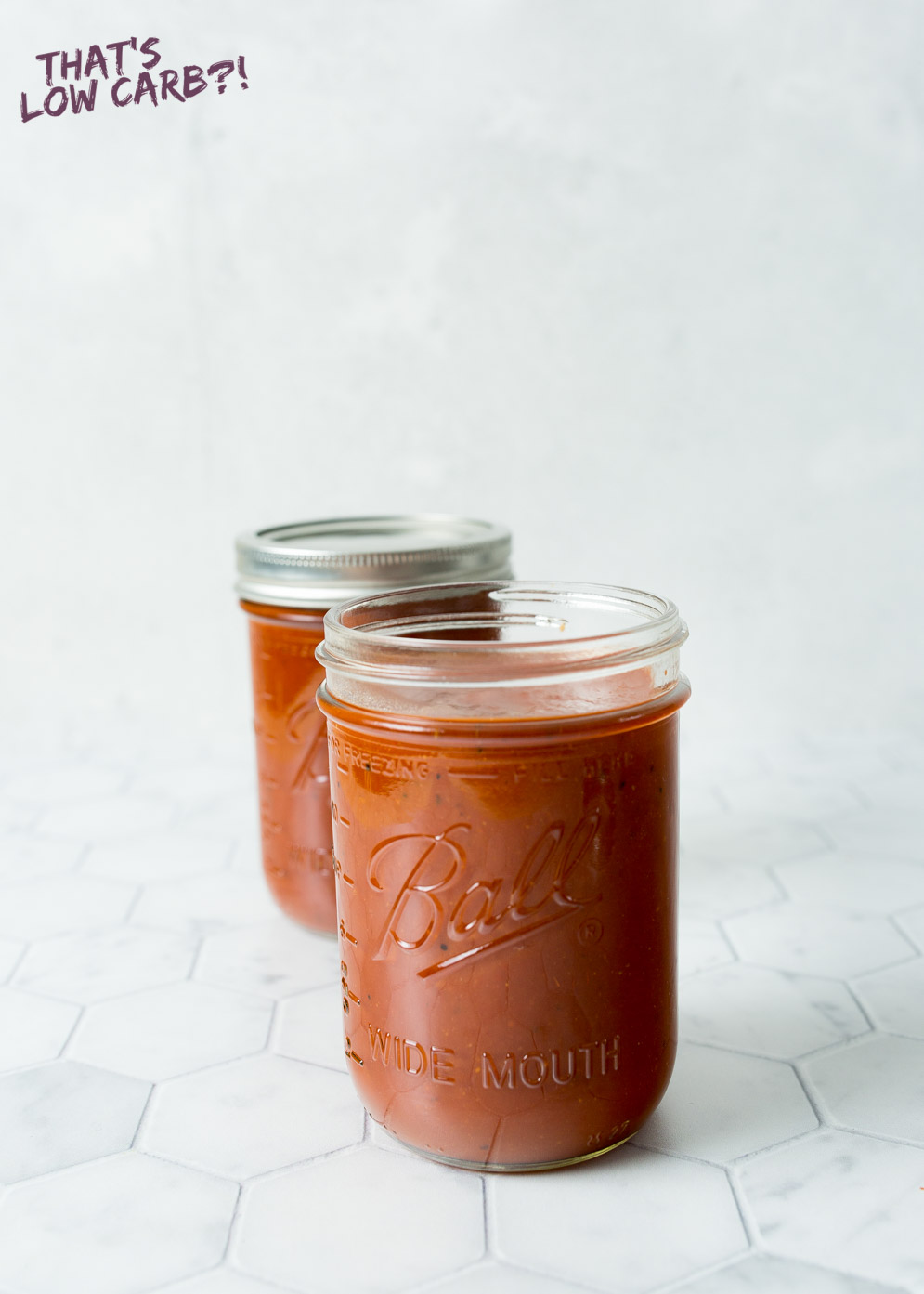 Vertical shot of low carb barbecue sauce jars filled with barbecue sauce in mason jars with white background