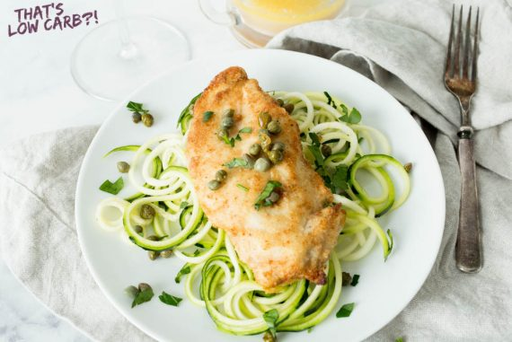 Chicken breast over zucchini noodles on white plate