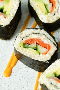 Smoked Salmon sushi rolls on a plate with orange sauce